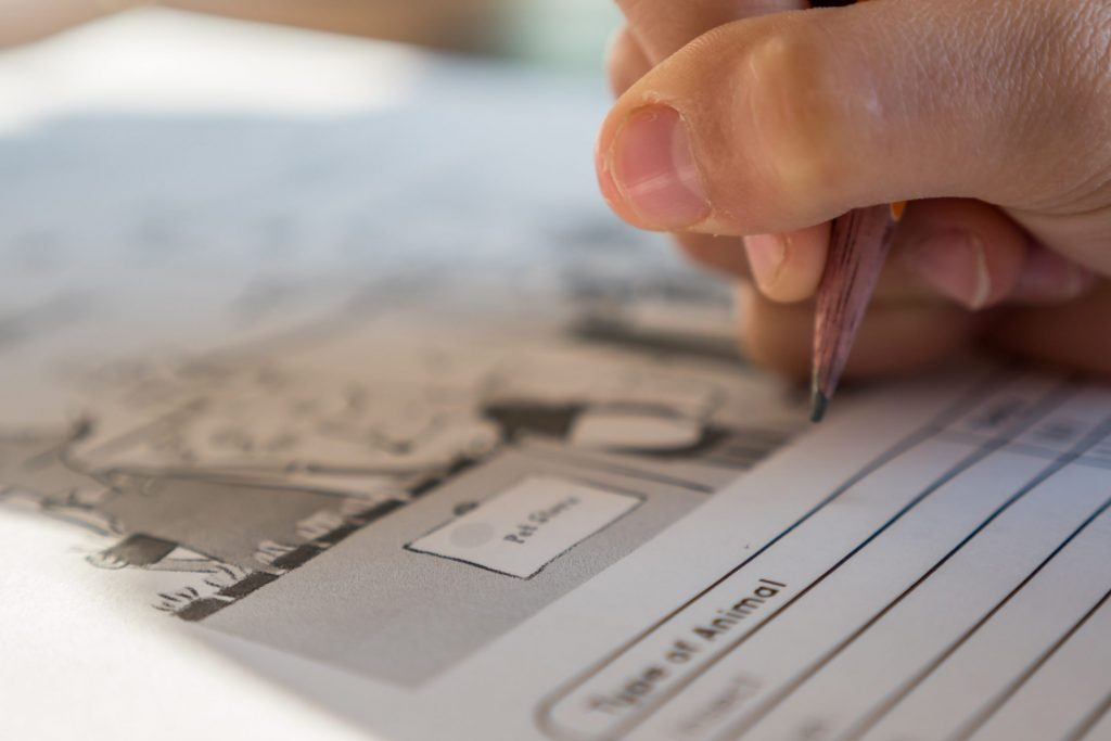 A person's hand holding a pencil hovers over a worksheet.