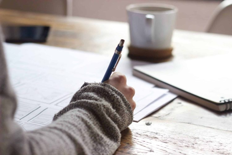 A person is writing, we see only their hand (holding a pen) and sleeve (it looks like they're wearing a comfy cardigan). On the table in front of them are worksheets, a notebook, and a coffee or tea mug.