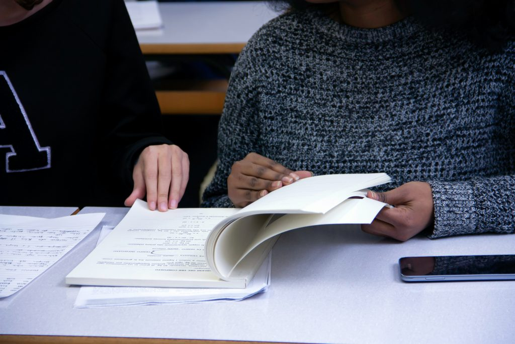 We see the upper torsoes of two high school students at a desk looking at notes in a notebook.