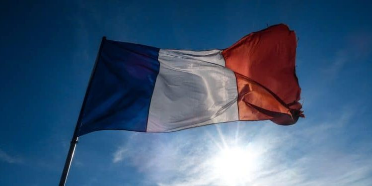 A French flag blows in the wind against a bright blue, sunny sky.
