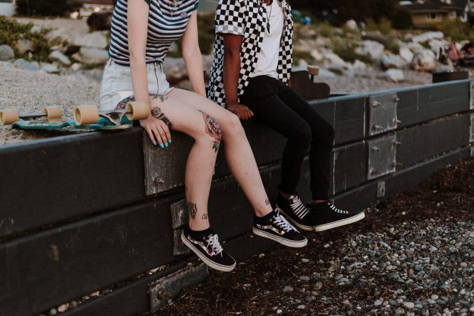 We see the bodies of a young woman wearing shorts and black sneakers, with tattooes on her legs, and a young man with long pants, black sneakers, and a black and white checked button-down shirt open to a t-shirt. They are sitting on a ledge by landscaping in what looks like a park. A skateboard sits next to the girl.