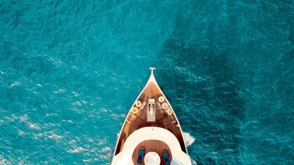 The prow of a luxury yacht cuts through turquoise water.
