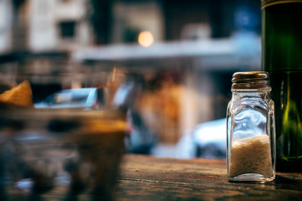 A salt shaker sits on a table in what may be a restaurant. It is the only clear thing in the photo, everything else is blurred. A bit existential.