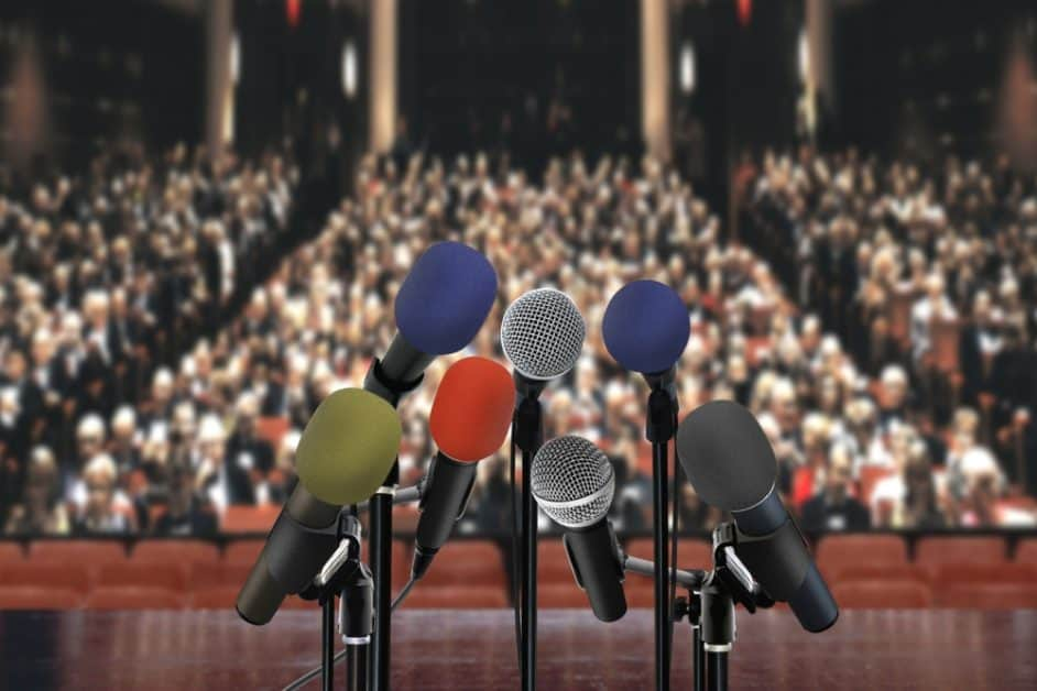 Several microphones point towards the viewer, as if they are going to give a speech to the seated crowd assembled behind them, sitting in stadium-style seating in what looks like a government building (the mics are in sharp focus but the rest of the view is blurry).