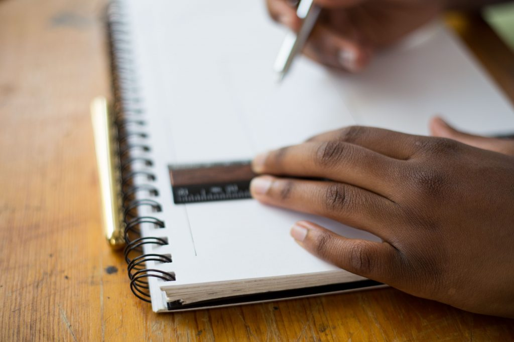 A person's hands carefully hold a ruler and a pen on a notebook.