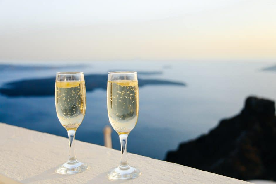 At sunset, two glasses of sparkling wine sit on a balcony ledge overlooking the ocean and several rocky island-like formations scattered over its surface.