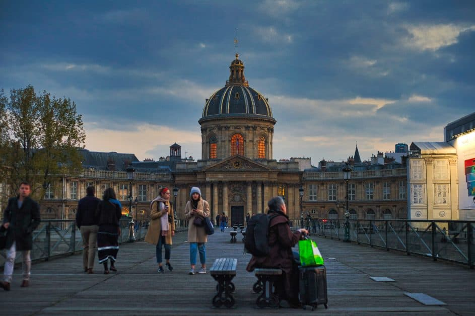 People walk along the Pont des Arts and a man is sitting on a bench in the middle with suitcases and a shopping bag. It's everyday life, not just tourism.
