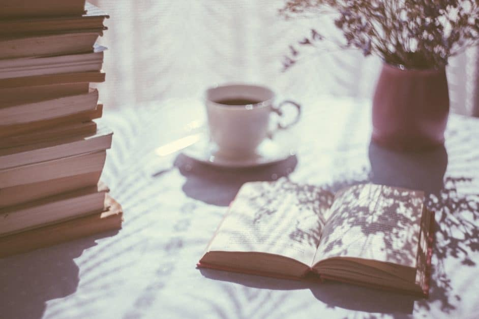 On the left, we see a tall pile of books. On the right in the background is a pot of flowers, possibly lavendar. The sunlight from the window in the background casts the flowers' shadows over the pages of an open book in the foreground. There is a white porcelain teacup full of tea in the middle, just behind the left corner of the open book.