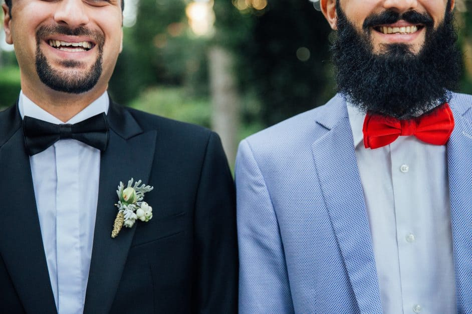 Two smiling bearded men stand side by side. We see them from their mid-nose, down. One is wearing a black tuxedo with a boutonniere , while other is in a light blue tuxedo with a red bowtie. The photo radiates happiness.
