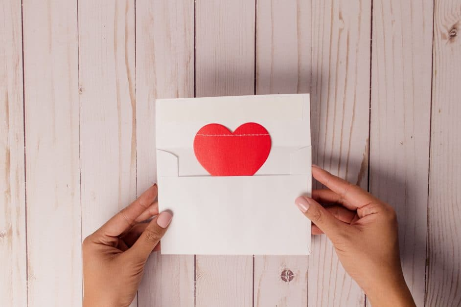 A woman's hands hold an open envelope from which a red paper heart emerges.