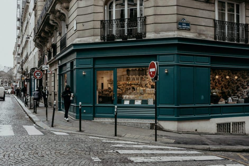 A mean wearing a hoodie walks in front of a wooden shopfront on a dreary day on a typical Parisian street.