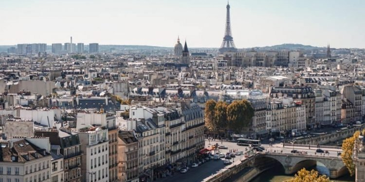 View of Paris, probably taken from the towers of Notre-Dame. We see many typical, Haussmannian-style Parisian buildings, as well as landmarks like the Eiffel Tower and Les Invalides. But we also see cards and buses in the streets below, and less aesthetic buildings in the distance.