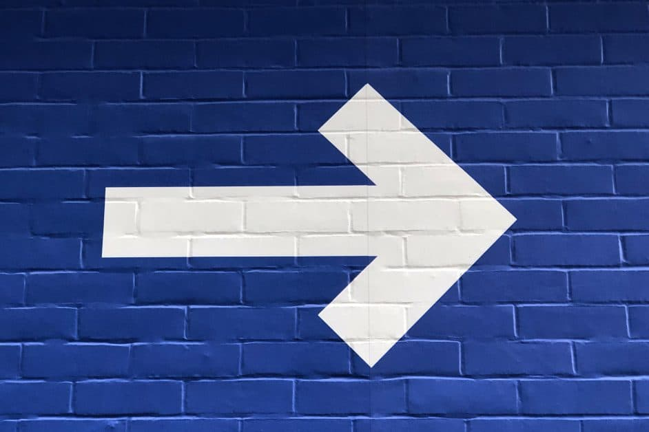 A white arrow painted on a blue-painted brick wall.