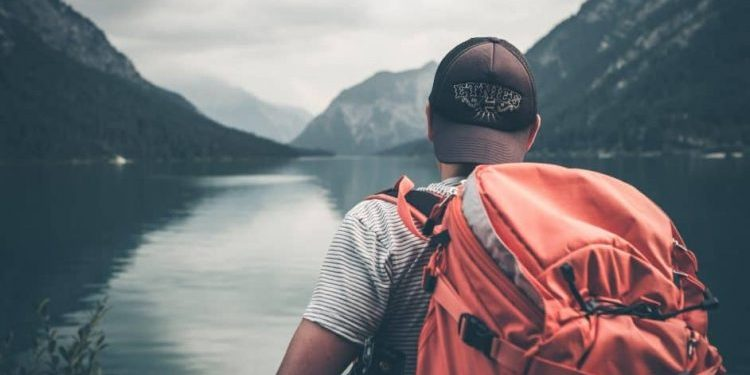A man with a backwards cap and a full backpackers backpack takes in the beautiful view before him of a mirror-gray lake surrounded by mountainst that slope gently down towards it.