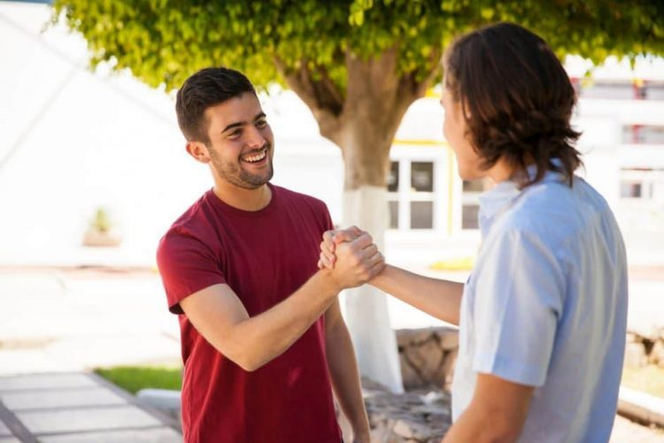 "Two young guys greet each other by clenching hands. We see only the back of one, and the torso and smiling face of the other. It's easy to imagine them asking each other, ""Ça va, mon pote ?"""