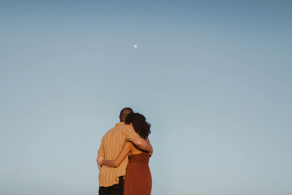 A man and a woman hold each other and look at teh sky, where the moon appears to be, although it's daylight. The blue sky takes up most of the frame.