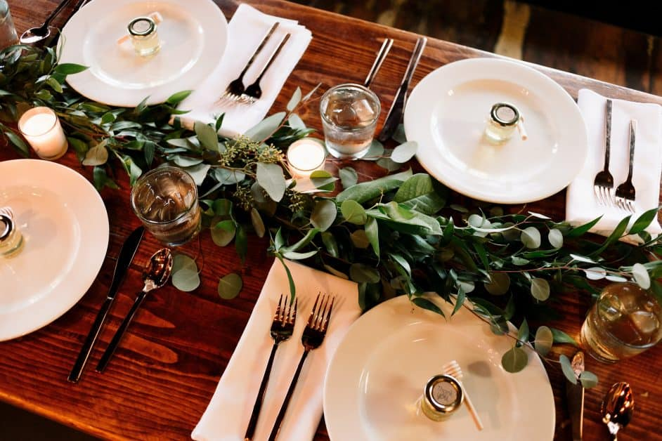 A beautiful table setting, with white plates with little glass honey pots in their centers. A long leafy branch is the centerpiece. The wood of the table is a warm, reddish brown.