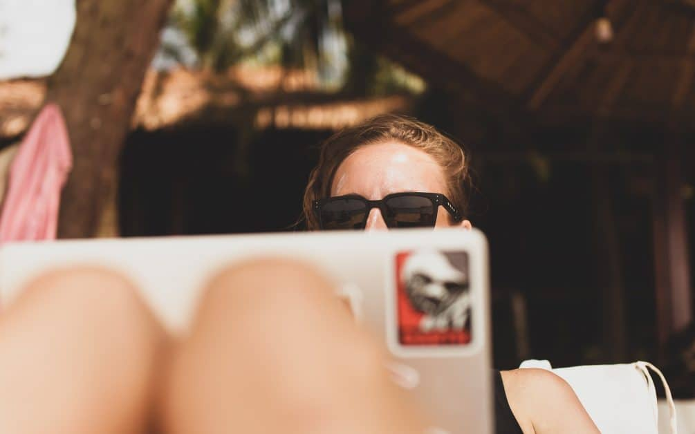 A woman is outside on her laptop. We see the back of the laptop screen against her knees. She's wearing sunglasses and the bottom of her face is hidden by the laptop screen.