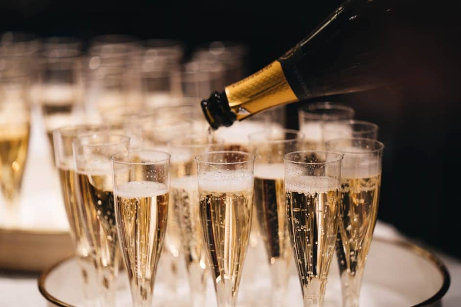A champagne bottle is titled towards a number of champagne flutes on a tray, filling what seems to be the final one before the trays are brought out for what just might be a French New Year's celebration.