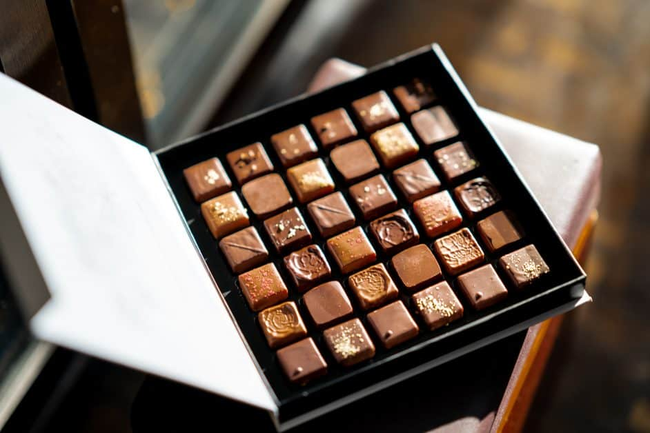 A box of chocolates open to reveal its delicious contents, all set in neat squares. Many of these chocolates have gold flake on them, so they seem pretty high-end.