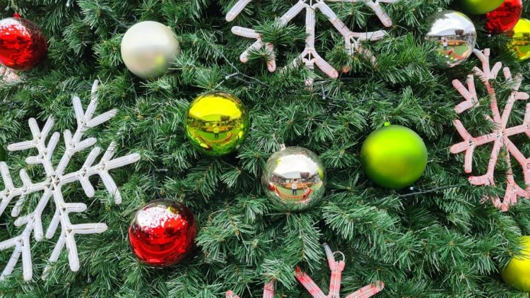 A close-up of a Christmas tree decorated with bright green and yellow, silver, and red Christmas balls, as well as large snowflake ornaments that look like they light up at night, some white and some red.