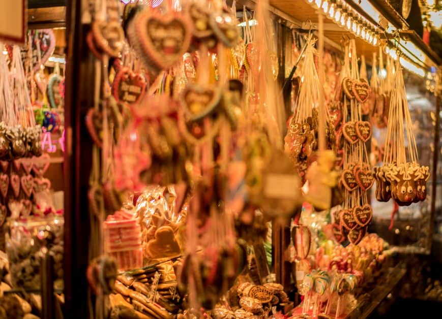 A stall at a Christmas market, brightly lit at night. It's full of candies and handmade wooden ornaments, especially heart-shaped ones that evoke German and Alsatian traditional crafts.