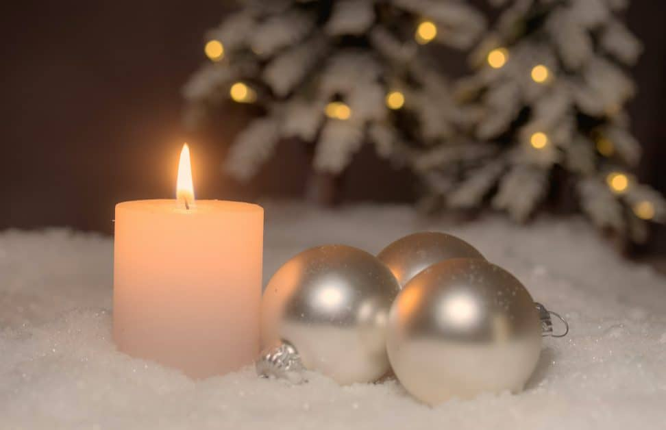 A white candle and a few whitish-silver Christmas balls in a small group sit on a bed of artificial snow. In the background is the bottom of a snow-covered and pine tree decorated with white Christmas lights.