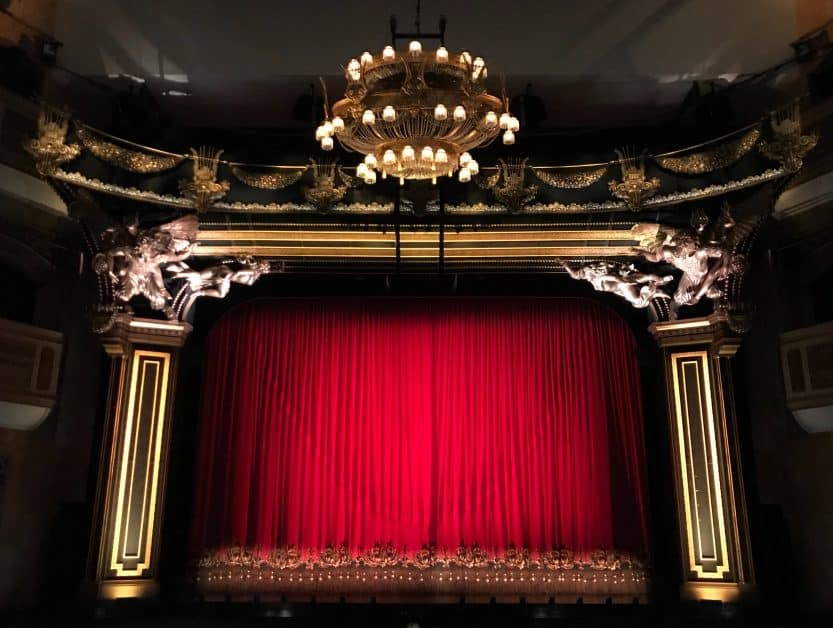 The stage of a theater, with its red curtains closed. There are an elaborate chandlier on the ceiling above the audience, and sculptures around the top of the stage.
