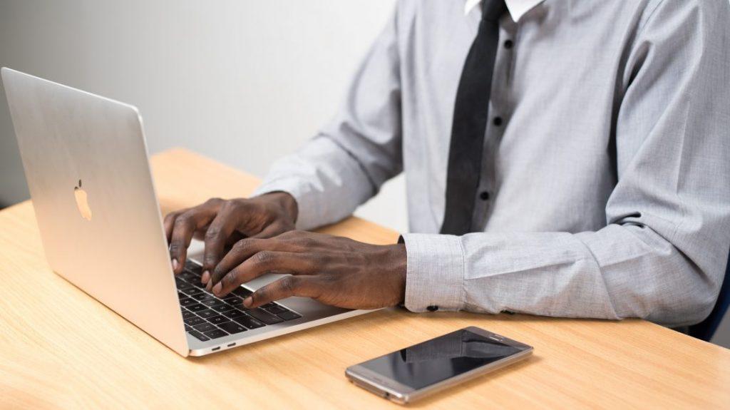 A man in a tie types on a laptop. We only see his torso, arms, and hands.
