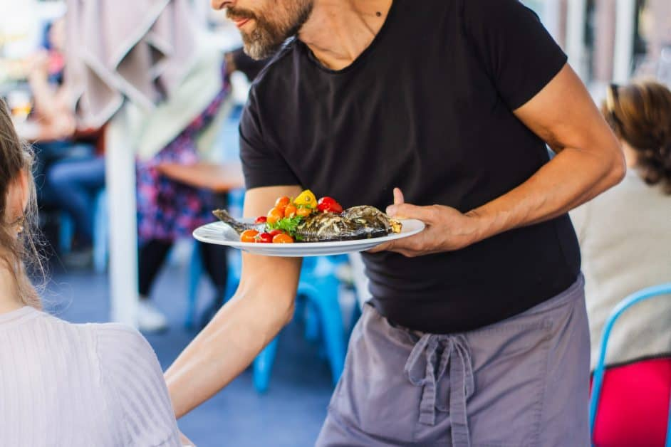 A waiter in a black t-shirt and gray apron serves a customer at a cafe terrace. The plate seems to contain fish and vegetables. We see the waiter from the lower jaw, to the knees. We see only a small part of the neck, ear, and upper torso of the customer, a woman.