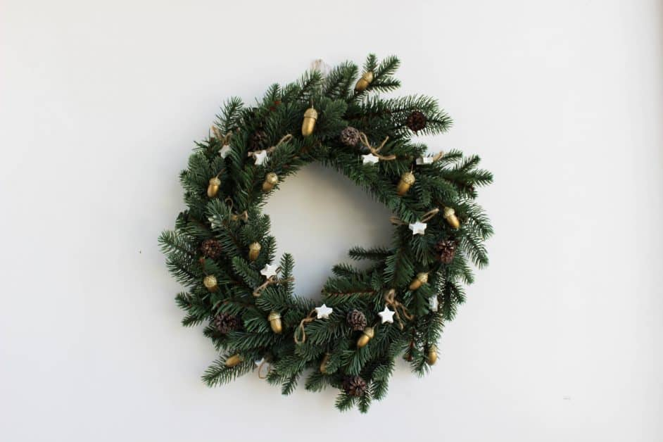 A holiday wreath of green pine, with golden acorn and white star decorations.