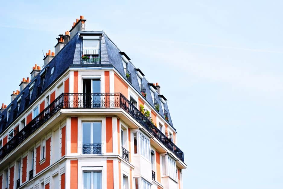 An orange-and-white painted Parisian apartment building with a gray roof, against a blue sunny sky.