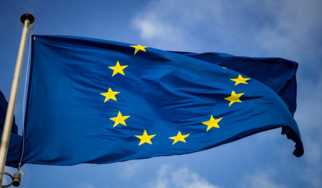 The flag of the European Union, dark blue with a circle of yellow stars, blows in teh wind against a blue, sunny sky.