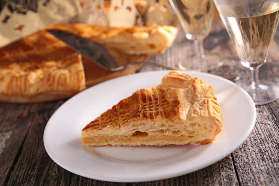 A slice of galette des rois (king cake), which in France is made with a flaky pastry outer layer and filled with frangipane that is, almond paste. There are glasses of what might be champagne in the background, as well as the rest of the king cake with a paper crown behind it.