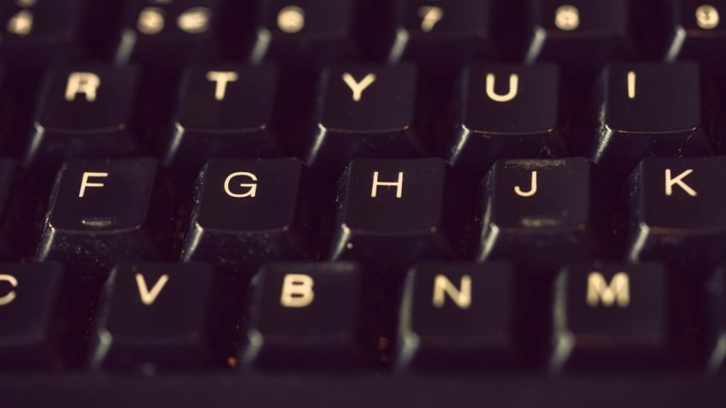 close-up of a computer keyboard. The keys are black with white letters.