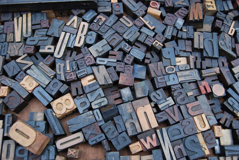 A large variety of letters and numbers for typesetting are splayed on a wooden surface. Tehy appear to be made of metal or wood.