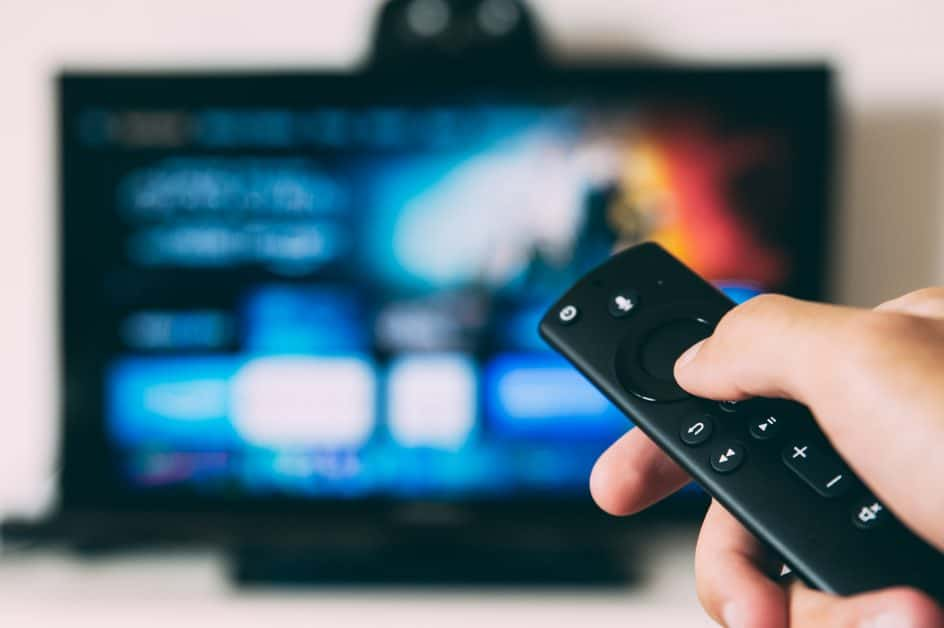 A person holds a remote control and aims it towards a TV. The screen is blurry but it looks like they are using a streaming service.