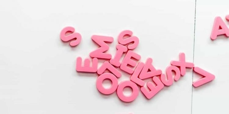 scattered pink plastic letters on a white background
