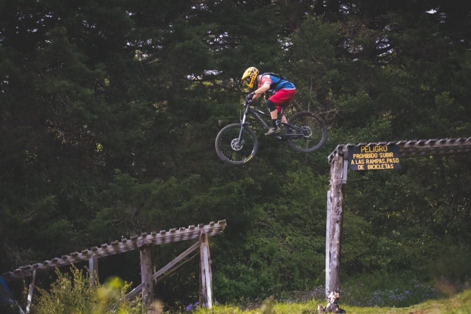 A person riding a bicycle jumps from one wooden platform to another.
