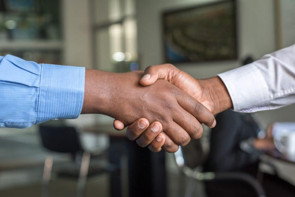 Two men shake hands. We see only their wrists and hands. In the background is a blurred view of what seems to be an office.