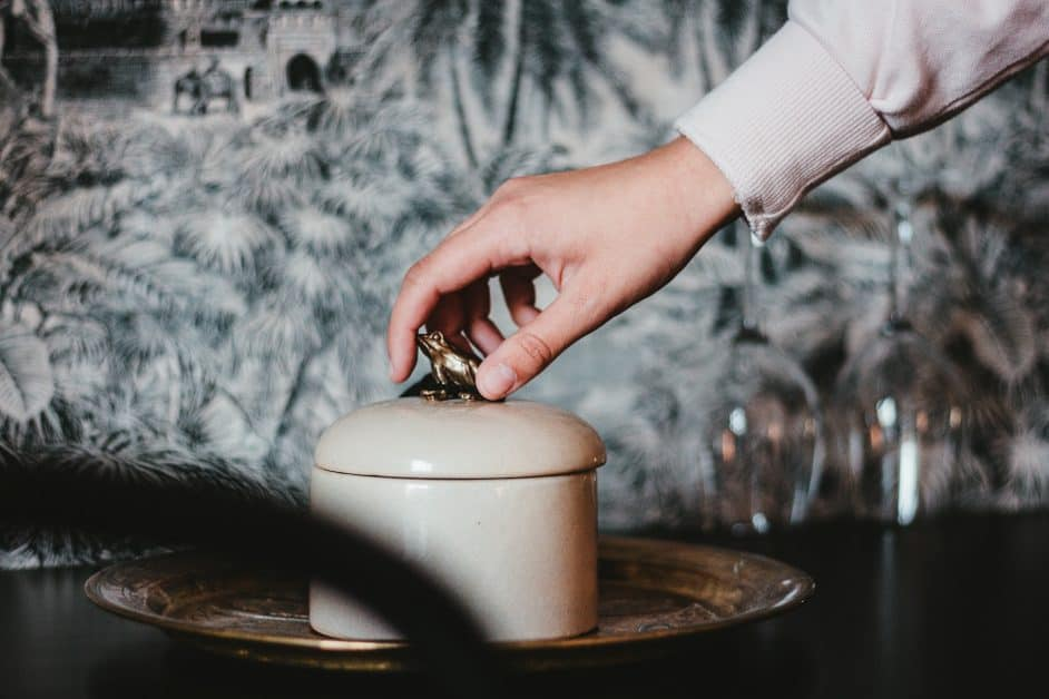 A person's hand reaches out towards the top of an elegant-looking ceramic jar whose lid is topped by a golden frog sculpture. Are they stealing the frog or what's inside the jar, or does it already belong to them?