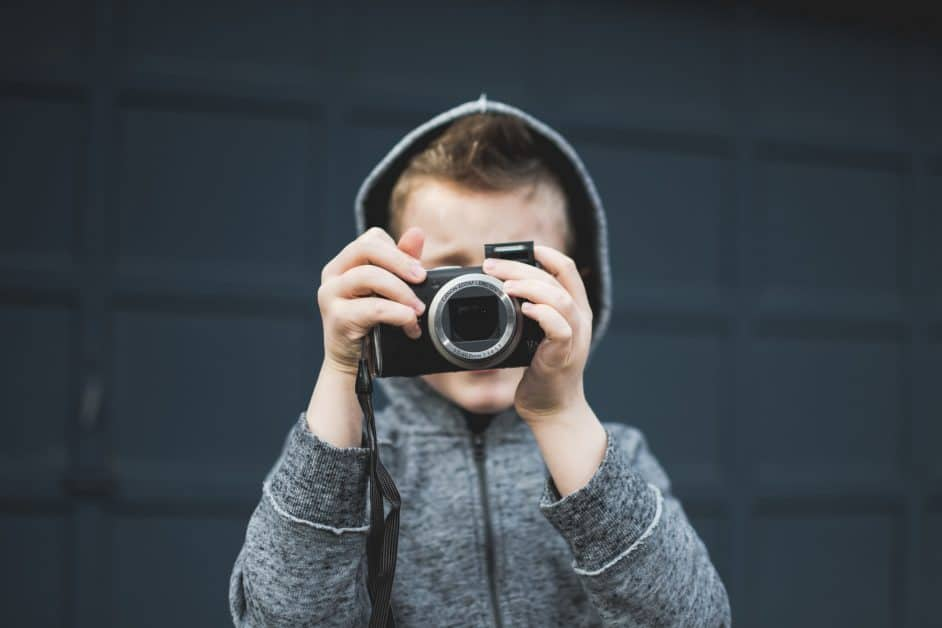 A little boy wearing a gray hoodie holds up a film camera and prepares to take a photo.