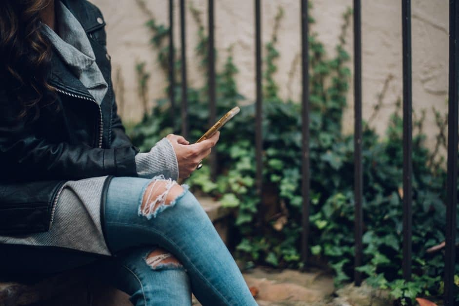 We see a seated woman from the neck down. She wears a leather jacket, gray sweater, and jeans deliberately ripped at the knees. She's using her phone to text or read a message. In the backgrond is ivy and metal gateposts. She may be sitting on steps.
