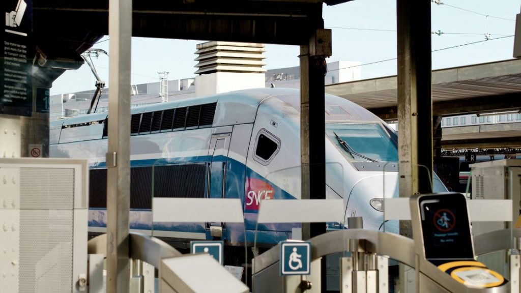 A TGV train waits at a train station. We can see the prominent logo of the SNCF towards the front of the train.