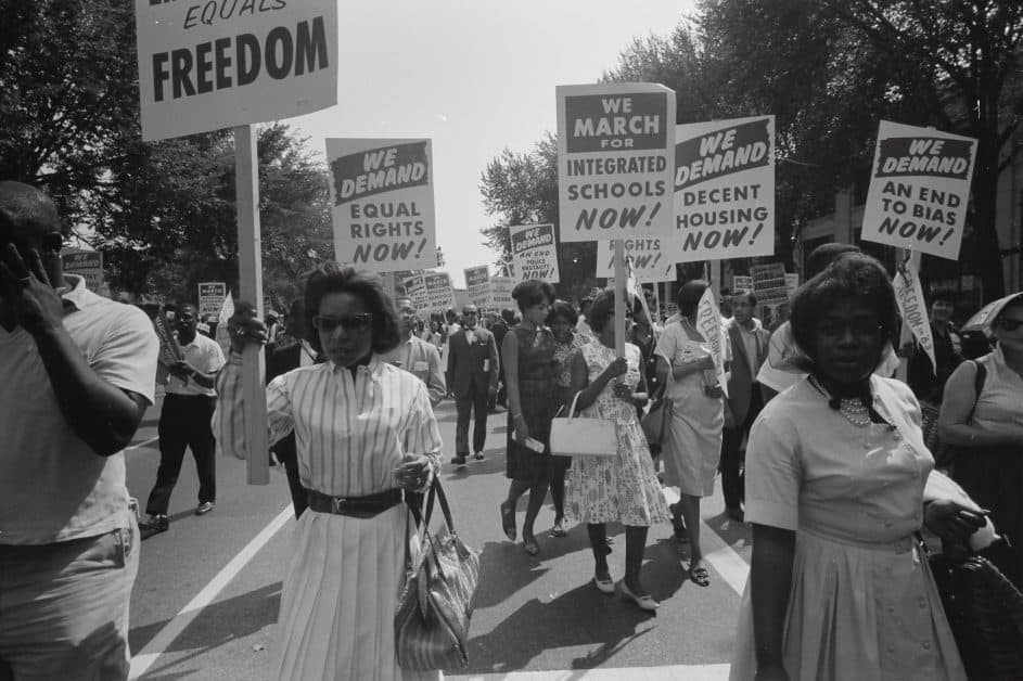 Image of a Civil Rigths march to improve housing, demand equal rights, and de-segregate schools in the US. The image is in black and white and shows a number of Black women and men marching.