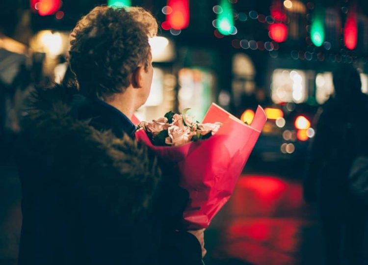 We see a man from the back, He's holding a bouquet of pink roses wrapped in red tissue paper. He's standing outside on what seems to be a city street. The background is blurry. His posture seems tense and watchful - maybe he's trying to spot his date!
