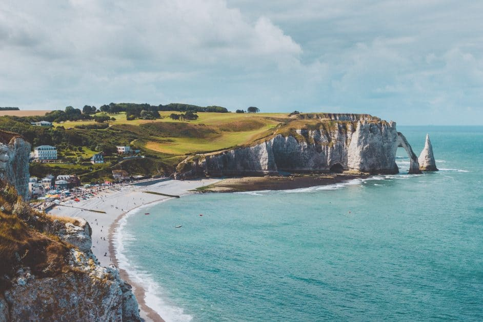 The coastline of Etretat, a city in Normandy, one of the most popular destinations in France for the French. The coast is known for its high white cliffs, including a natural archway that ends in the water near a conical white rock formation known as the Hollow Needle, if you're a fan of Arsene Lupin.