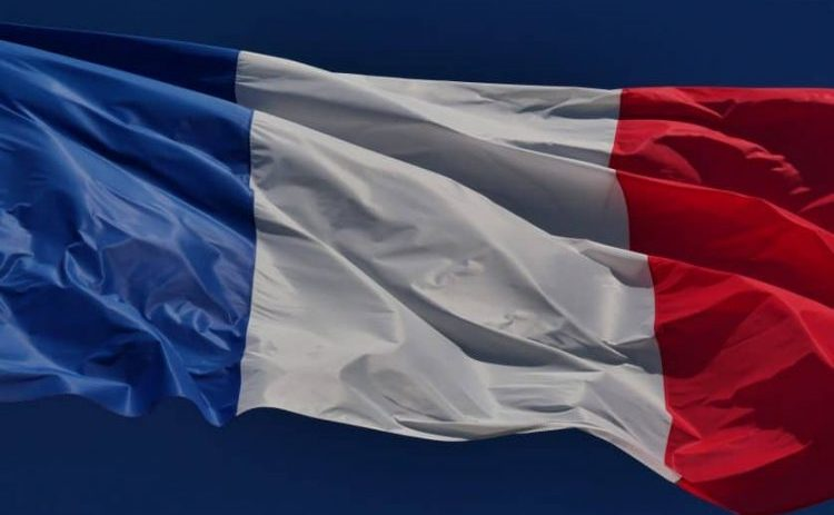 Closeup of a large French flag blowing in the wind against a dark blue, cloudless sky.