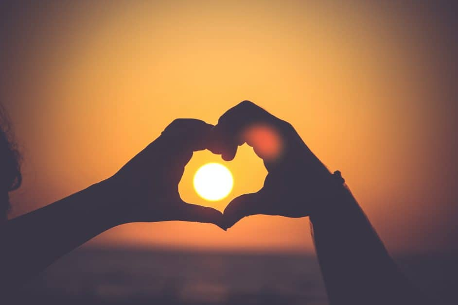At sunset, a person holds their hands which are in shadow up to the sky and makes a heart shape with them. It looks like the sun is in the center of the heart.