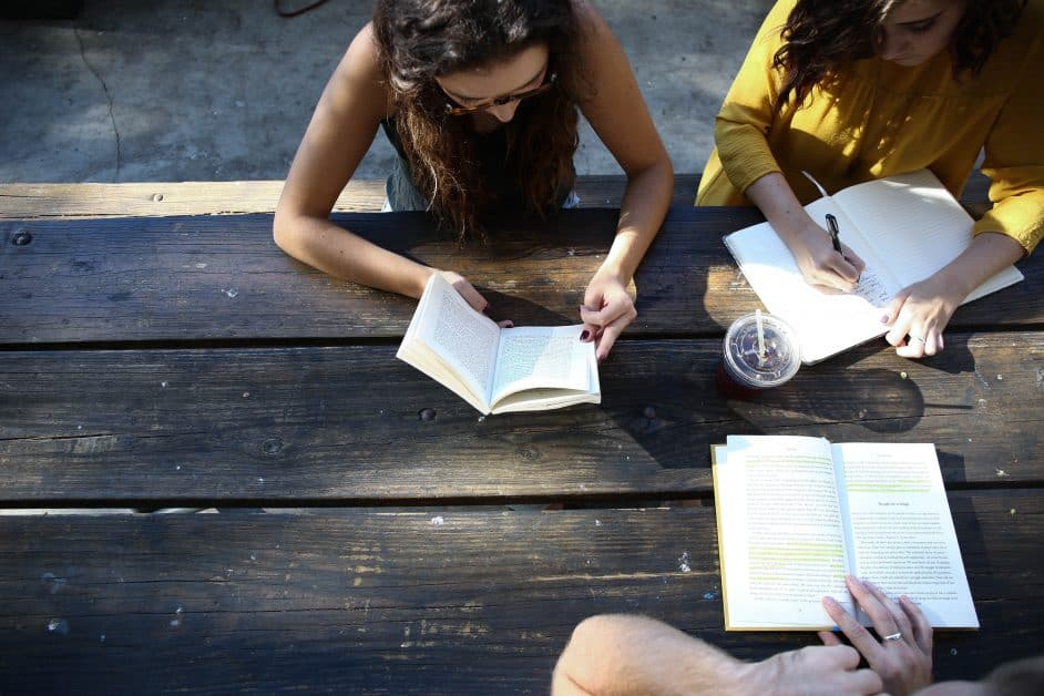 A view from above of two woman, one in a tank top and the other with long black hair and a yellow shirt, as well as a man but we only see his hands, studying at a table outdoors.